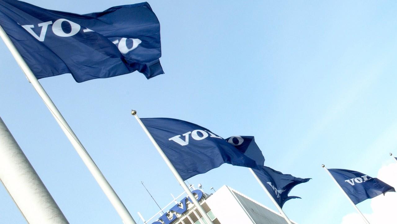 Quatre drapeaux du groupe Volvo flottent dans le vent avec un bâtiment Volvo en arrière-plan