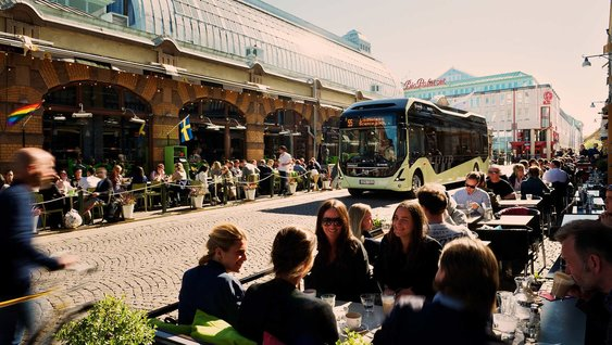 Volvo Group bus in the middle of a street surrounded by outdoor restaurant seatings filled with people