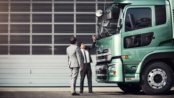 Two japanese Volvo Group employees inspecting a green UD truck