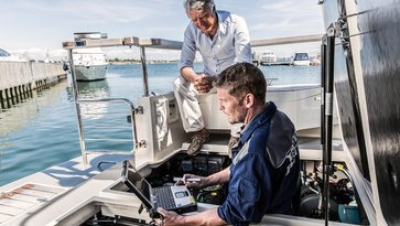 Volvo Penta worker diagnosing a boat with a computer while the boat owner looks on