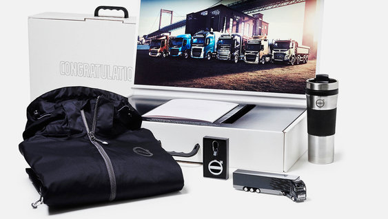 Volvo Group merchandise: jacket, coffee mug, Volvo truck toy, lighter, picture of Volvo trucks