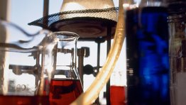 Chemistry set with a conical flask and beaker filled with a red liquid and a stand in the background