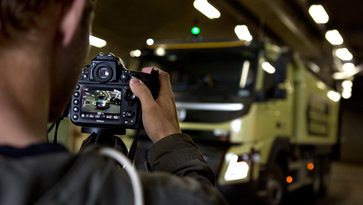 Photographer taking pictures of a white Volvo Group truck