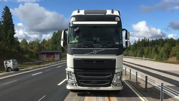 The front of a white Volvo truck driving on a road with an electric road system