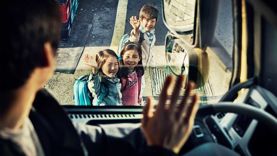 Man in a truck winking to children on the street | Report: Global Road Safety Scenarios