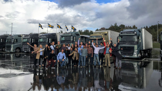 A Volvo Group team standing in front of seven Volvo trucks in Sweden