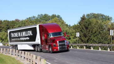 "Red Mack truck with the message ""I'm one in a million"" on its payload on a road in Allentown, USA"