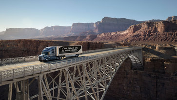 "Volvo truck with the message ""I'm one in a million"" on its payload, driving on bridge in San Diego, USA"