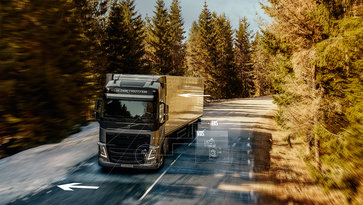 Grey Volvo truck driving on a snow covered road in a forest