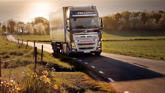Grey Volvo truck driving on a country road at sunset