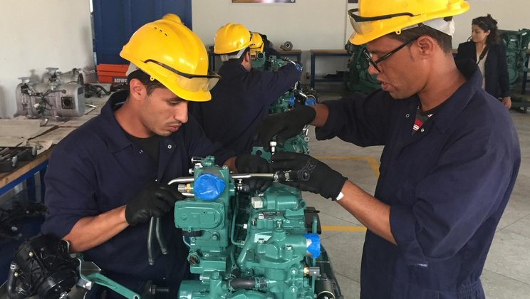 Students working with a Volvo engine
