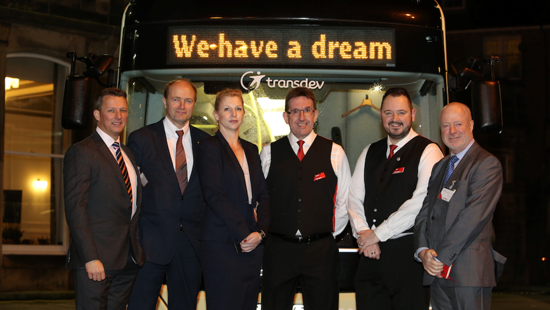 Six persons in front of a Volvo bus