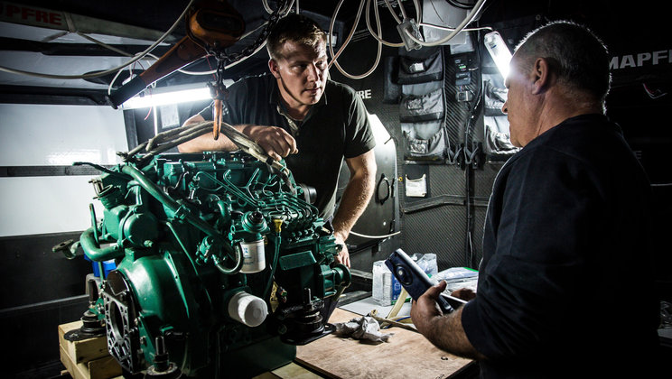Two men standing close to a Volvo Penta engine