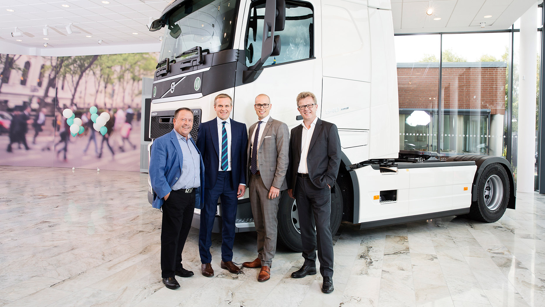 4 persons in front of a Volvo truck