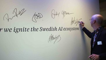Lars Stenqvist, Executive Vice President Group Trucks Technology, signing a whiteboard at AI innovation of Sweden
