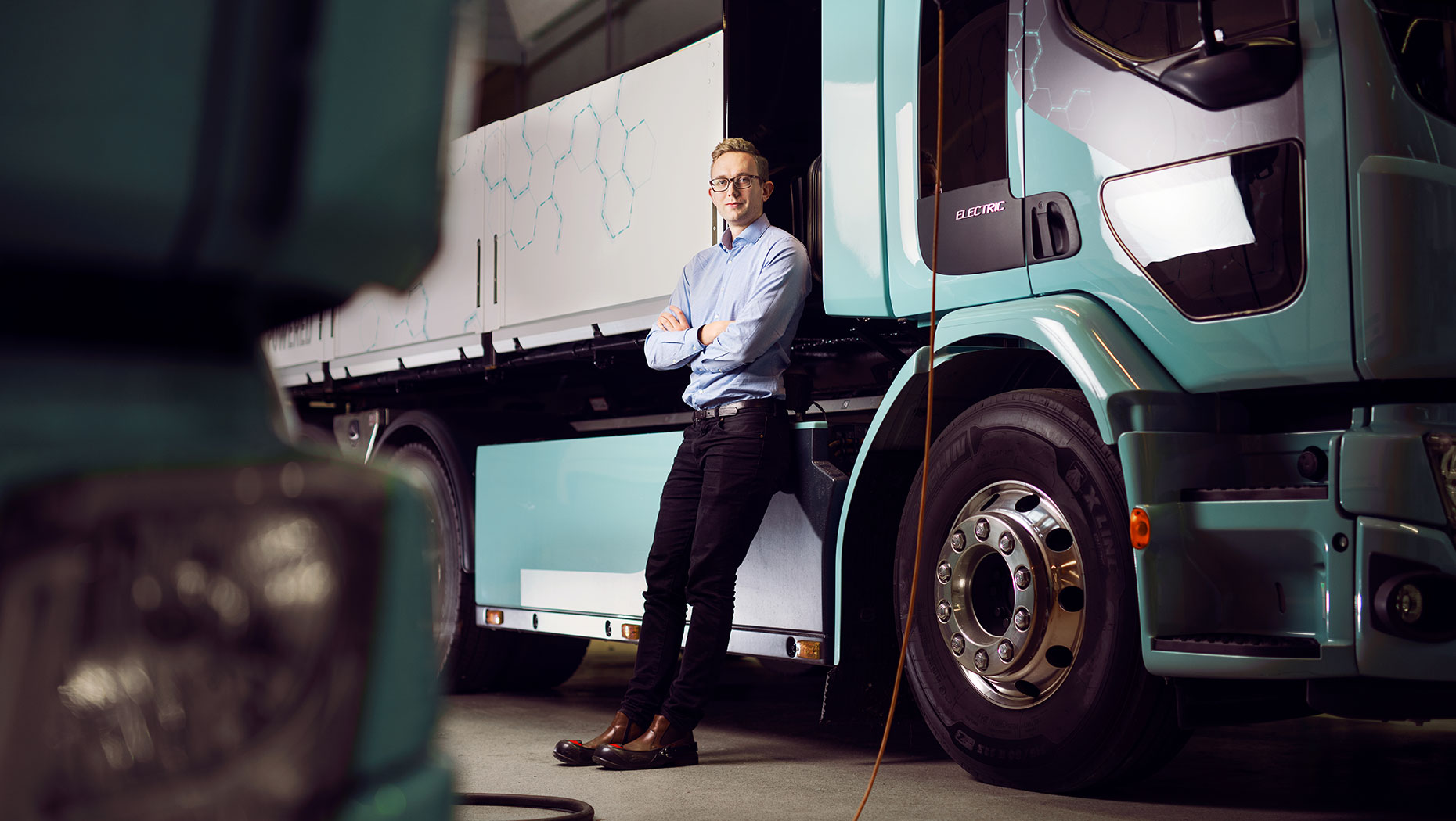 Rikard Vinge, Data Scientist at the Volvo Group, alongside one of Volvo's electric trucks