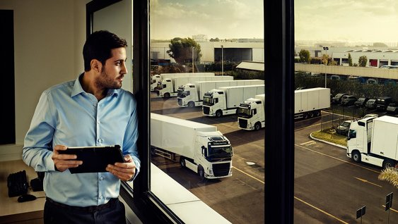 Volvo Group employee in a blue shirt looking out over a lot filled with white Volvo trucks
