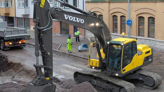 Yellow Volvo Group excavator digging at a road work site