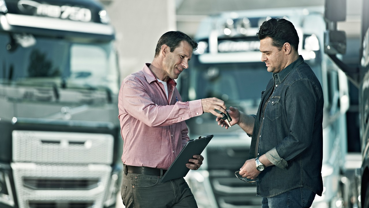 Volvo Group salesman handing over the key for a Volvo truck to a customer
