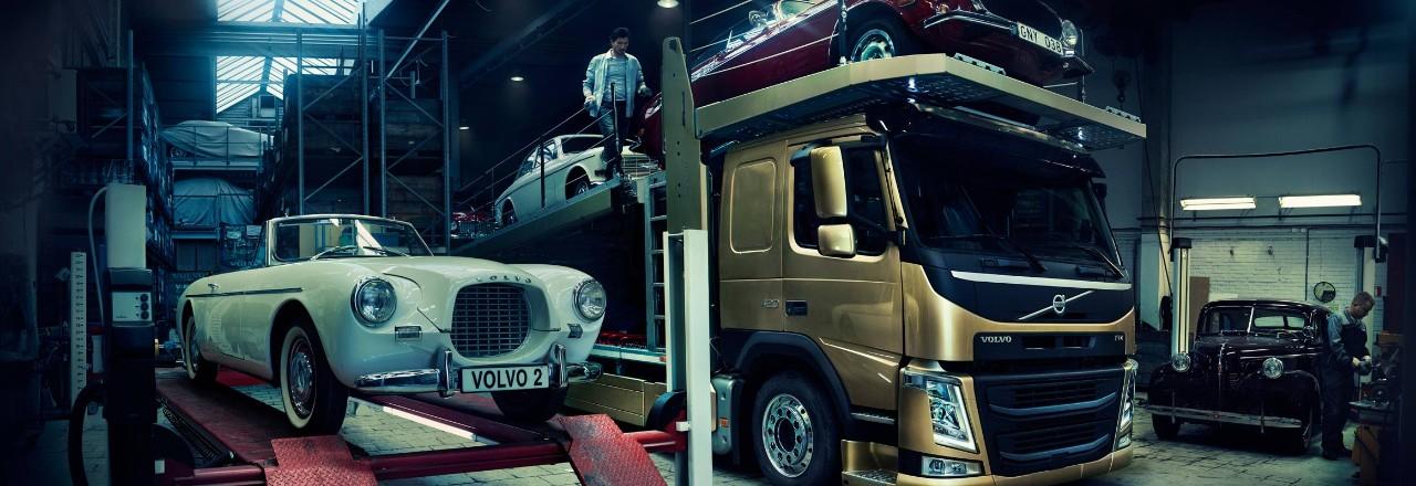 Ancienne voiture particulière Volvo de couleur blanche sur un stand à côté d'un camion Volvo de couleur bronze transportant une voiture particulière rouge et une autre de couleur blanche
