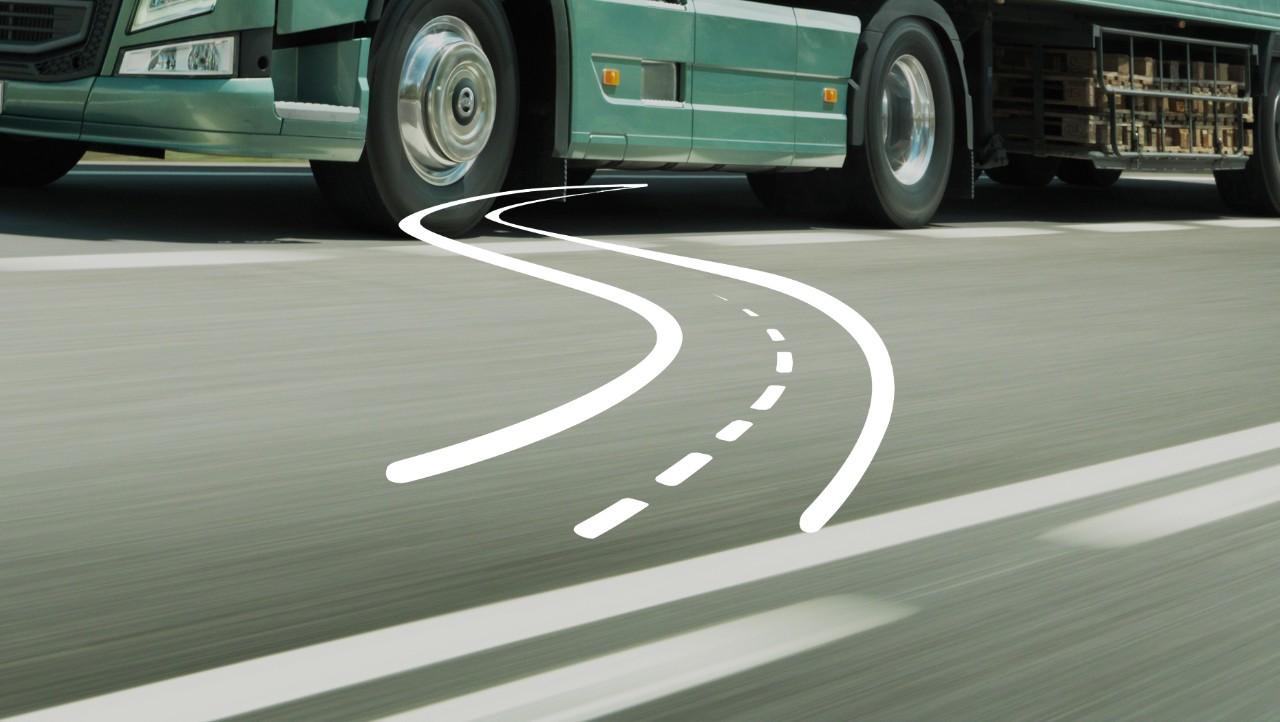 Een witte afbeelding van een kronkelige weg geplaatst over een groene truck van de Volvo Group op de weg