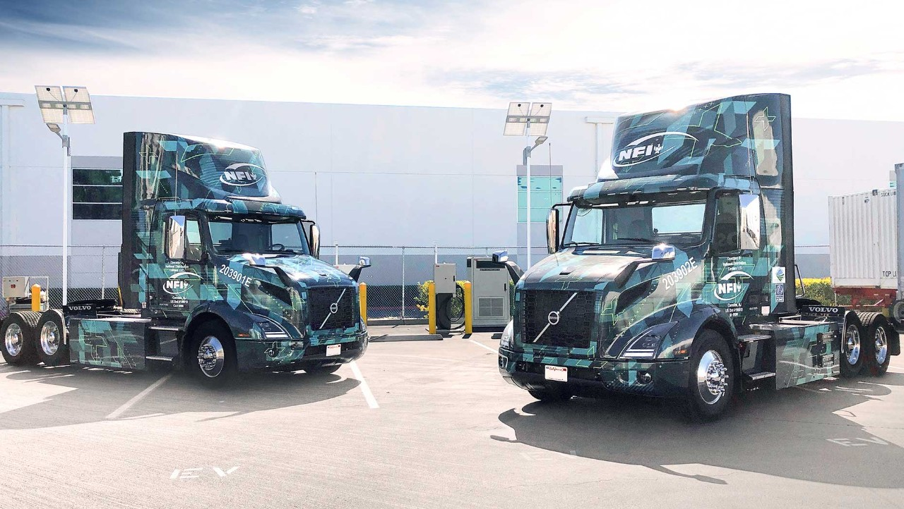 Volvo VNR Electric models parked in front of 150 kW chargers at Volvo Trucks customer NFI's Chino, California facility