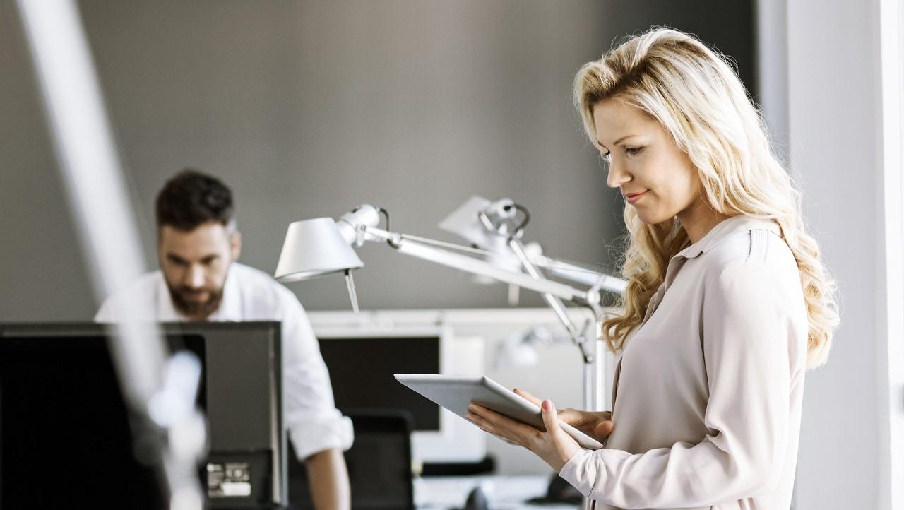 Dos empleados de Volvo Group, uno trabajando en su tableta, el otro trabajando en su computadora