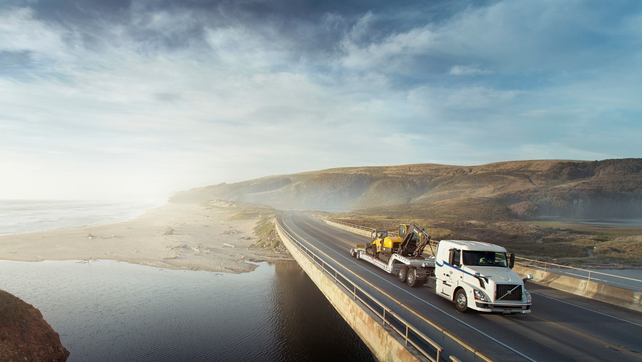 White Volvo truck on a bridge carrying a yellow excavator