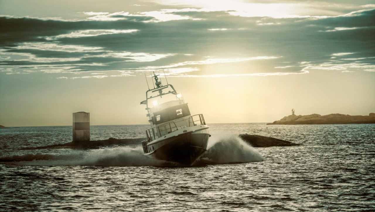 Duża motorówka robi ostry zakręt, tworząc wielką falę na morzu